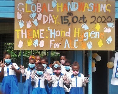 Students with facemarks in front of Global Handwashing Day sign in Solomon Islands