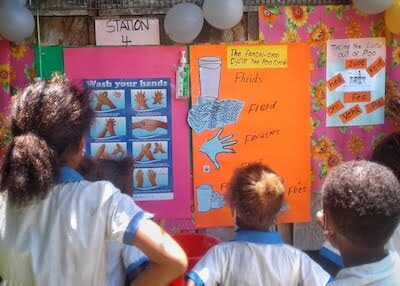 Students reading information about Global Handwashing Day