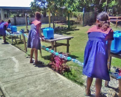 Students washing their hands with soap at safe distance from each other