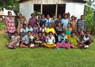 A group of women who participated in the Live & Learn workshop pose together on the grass