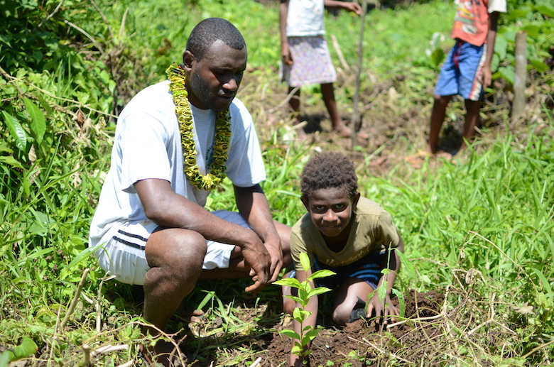 A man and boy planting a tree in a community owned protected forest