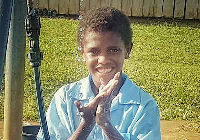 Boy washing his hands with soap at new facility in his school in Solomon Islands